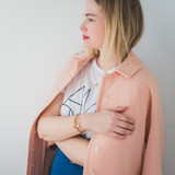 woman looking off to the side, wearing a pink coat and sterling silver oval locket with feather.