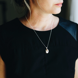 Elegant woman in black shirt wearing sterling silver oval necklace. The necklace is a locket that holds up to two photos inside.