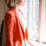 woman in blazer wearing a lapel pin.