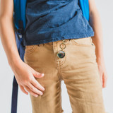 boy with a bronze photo locket keychain clipped to his khaki shorts with a photo of his family inside the locket pendant