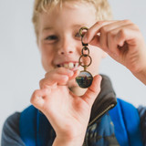 little boy holding a keychain photo locket that can clip to backpacks, purses, keychains, great for kids