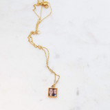 Gold open square locket with gold chain, laying on marble table