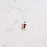 Square photo locket and silver chain, laying on a marble table