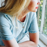 blonde woman looking out window, wearing silver square locket