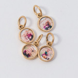 Four gold charms from the Charm Locket with out the chain on.