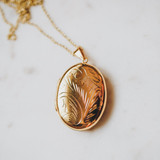 gold locket with etching that holds one or two photos inside