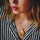 woman wearing gold locket