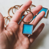 hand holding a keychain pendant locket design for a purse or backpack or keys with a hopeful message written in blue