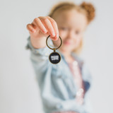 """little girl holding a locket pendant with a design that says """"more love"""""""