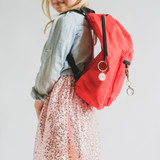 kindergarten-aged girl wearing a red backpack with pendant clips that have positive messages