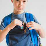 2nd grade boy putting a positive message keychain pendant locket into his pocket before school locket sisters