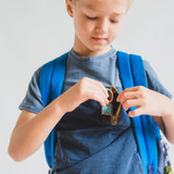 young boy with blue shirt and blue backpack putting a positive message keychain into his pocket