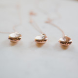 three rose gold lockets that are round, petite, small, dainty, and durable