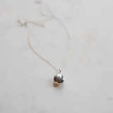 small silver Edith Locket on white marble to demonstrate bale size and modern, clean design