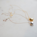 one gold and one silver edith locket on marble