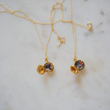 two open photo locket keepsake necklaces on marble