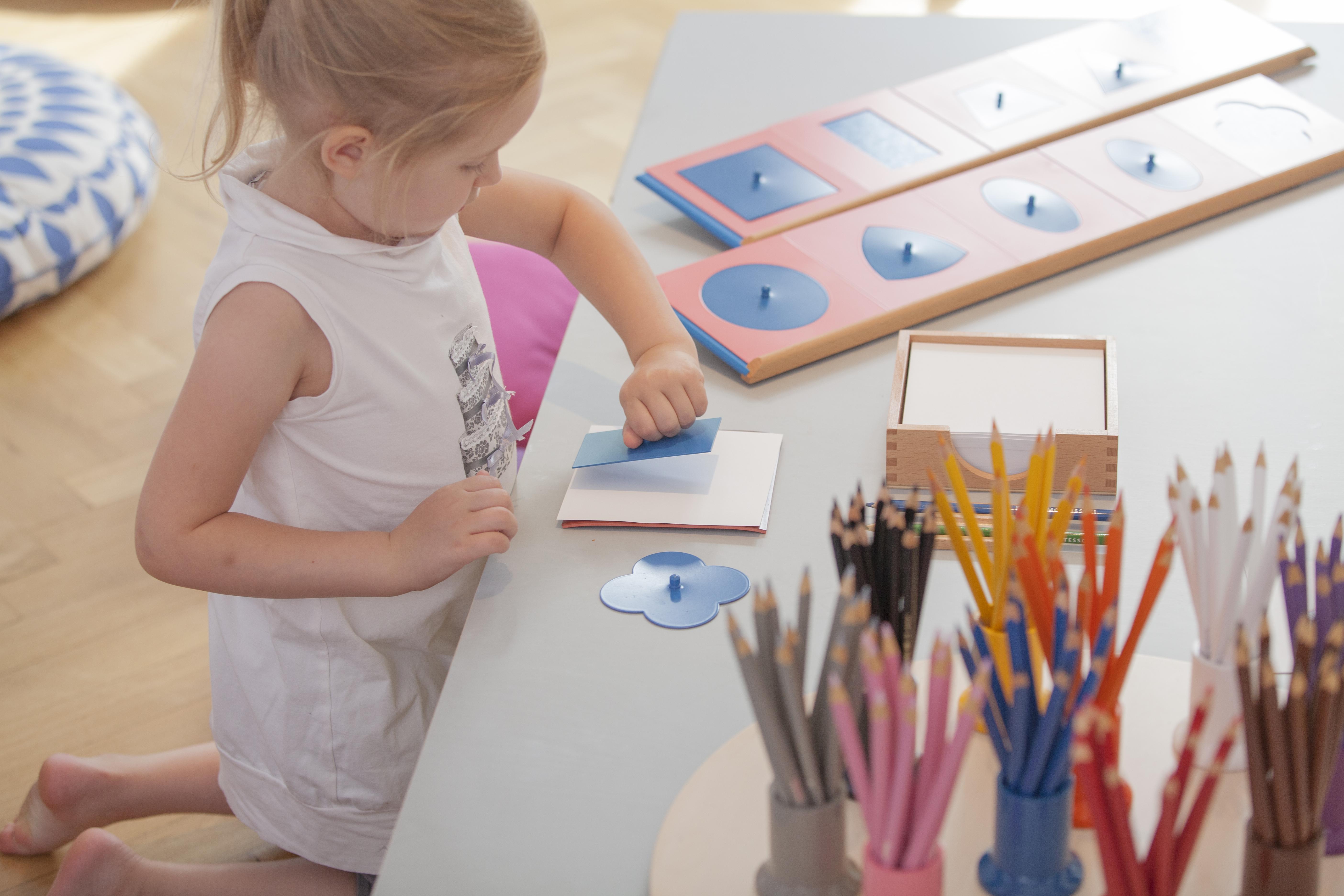 preschooler kneeling playing with Nienhuis Montessori equipment