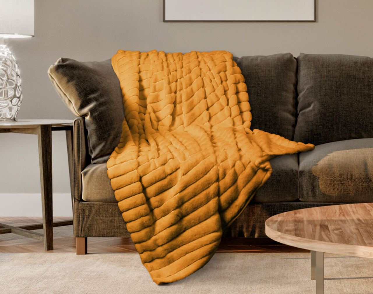 The Ribbed Faux Fur Throw in Honey, a warm orange, draped over a couch.