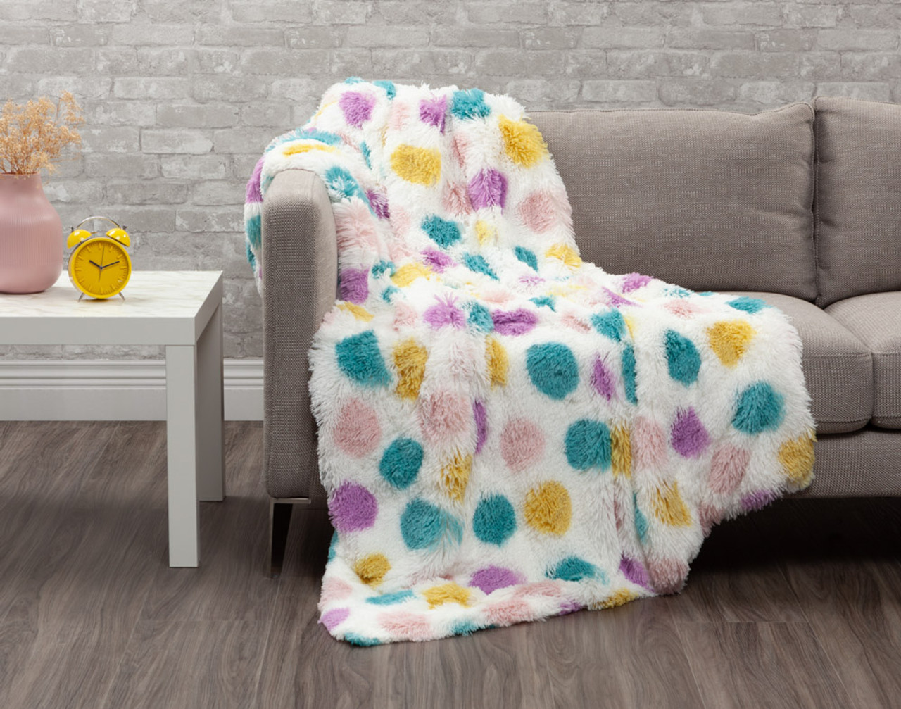 Our Frosted Shaggy Throw in Dots features purple, pink, blue, and yellow polka dots on a fluffy white background.