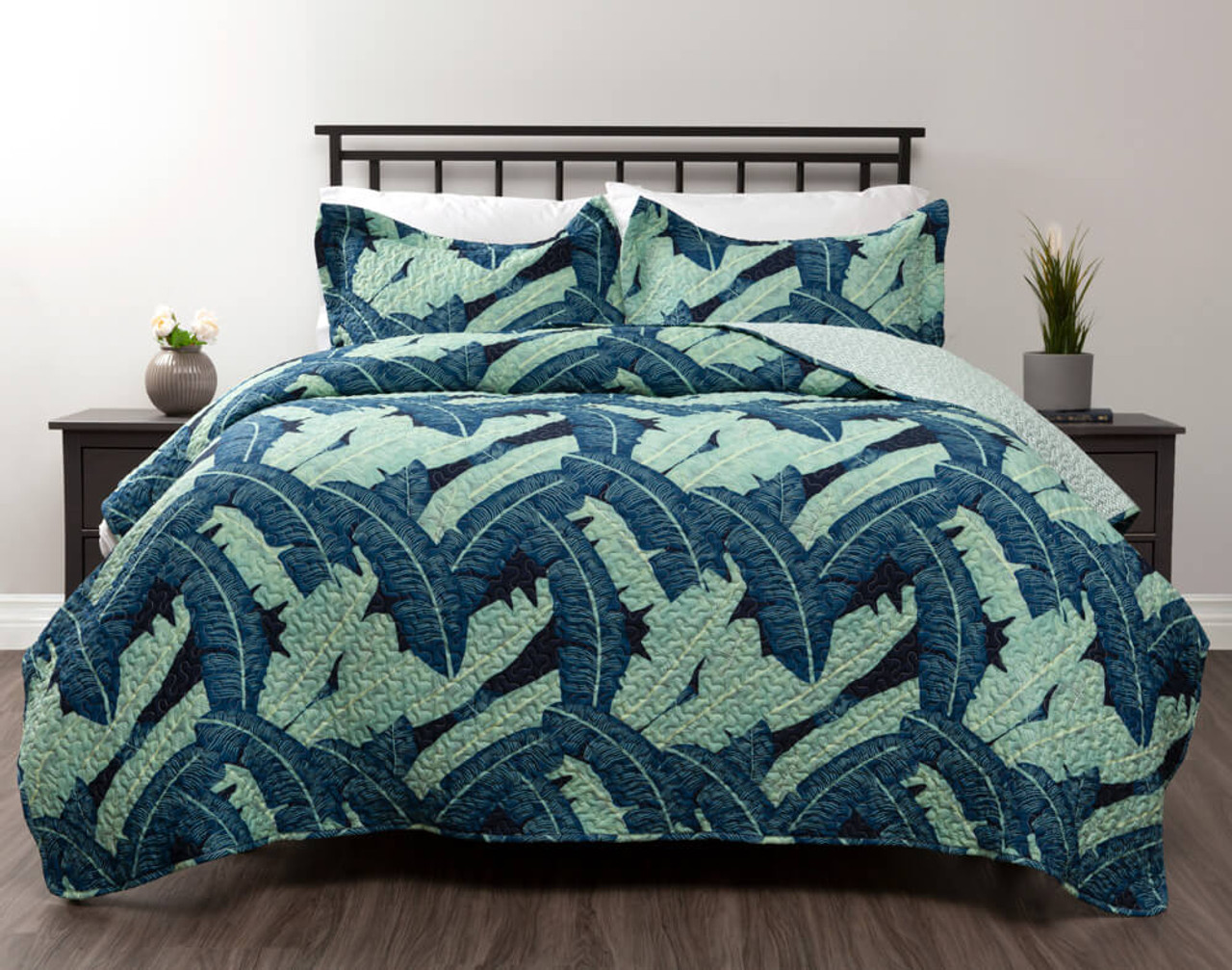 Malibar Coverlet Set featuring banana leaves in shades of sapphire blue and pale celadon green on a dark navy blue background.