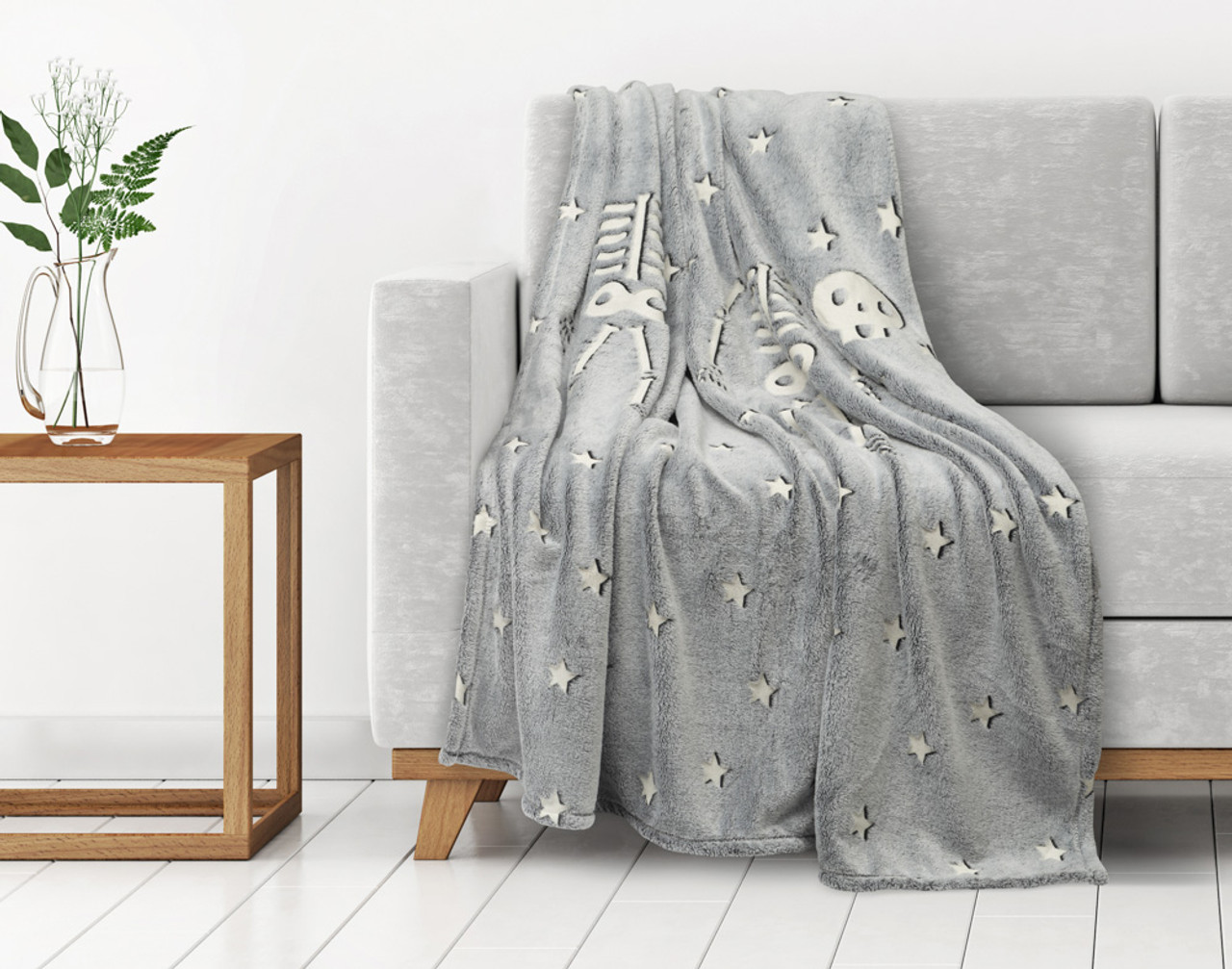 Skeleton Glow In The Dark Fleece Throw draped over a couch.