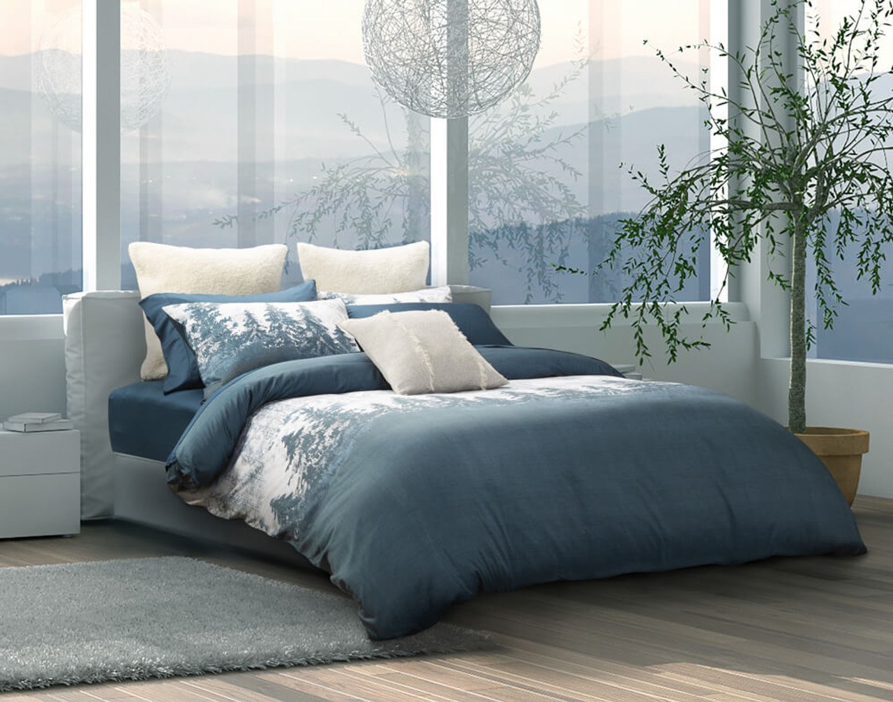Side view of our Alps Duvet Cover in a bright bedroom near windows.