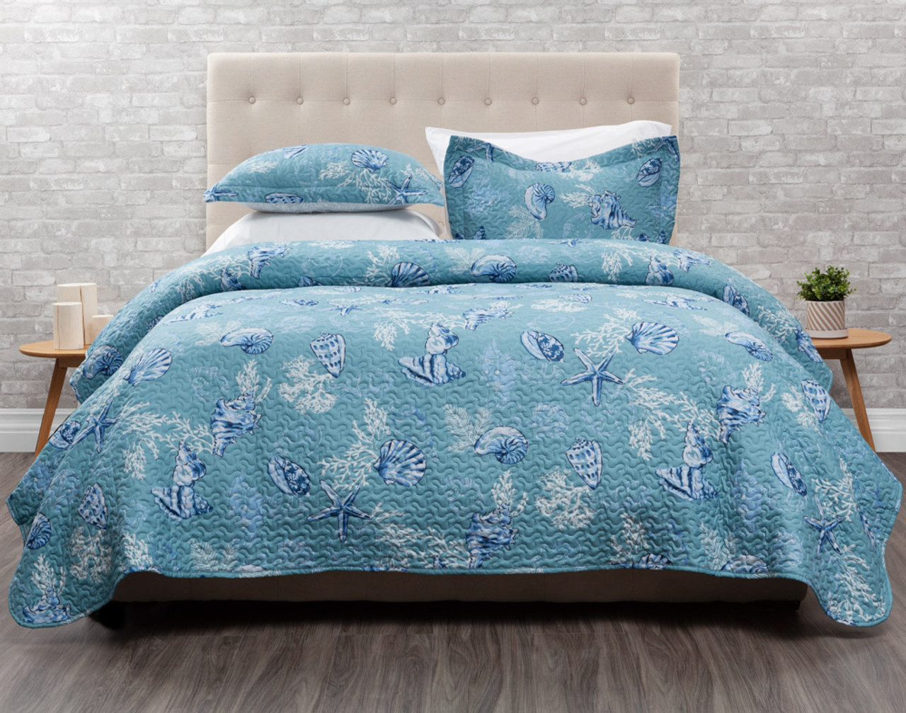 Shells Coverlet features blue and white seashells on an aqua blue background.