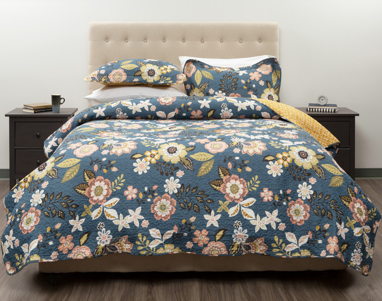 The Amita Cotton Quilt Set features gentle florals on a blue background, and reverses to a gorgeous yellow pattern.