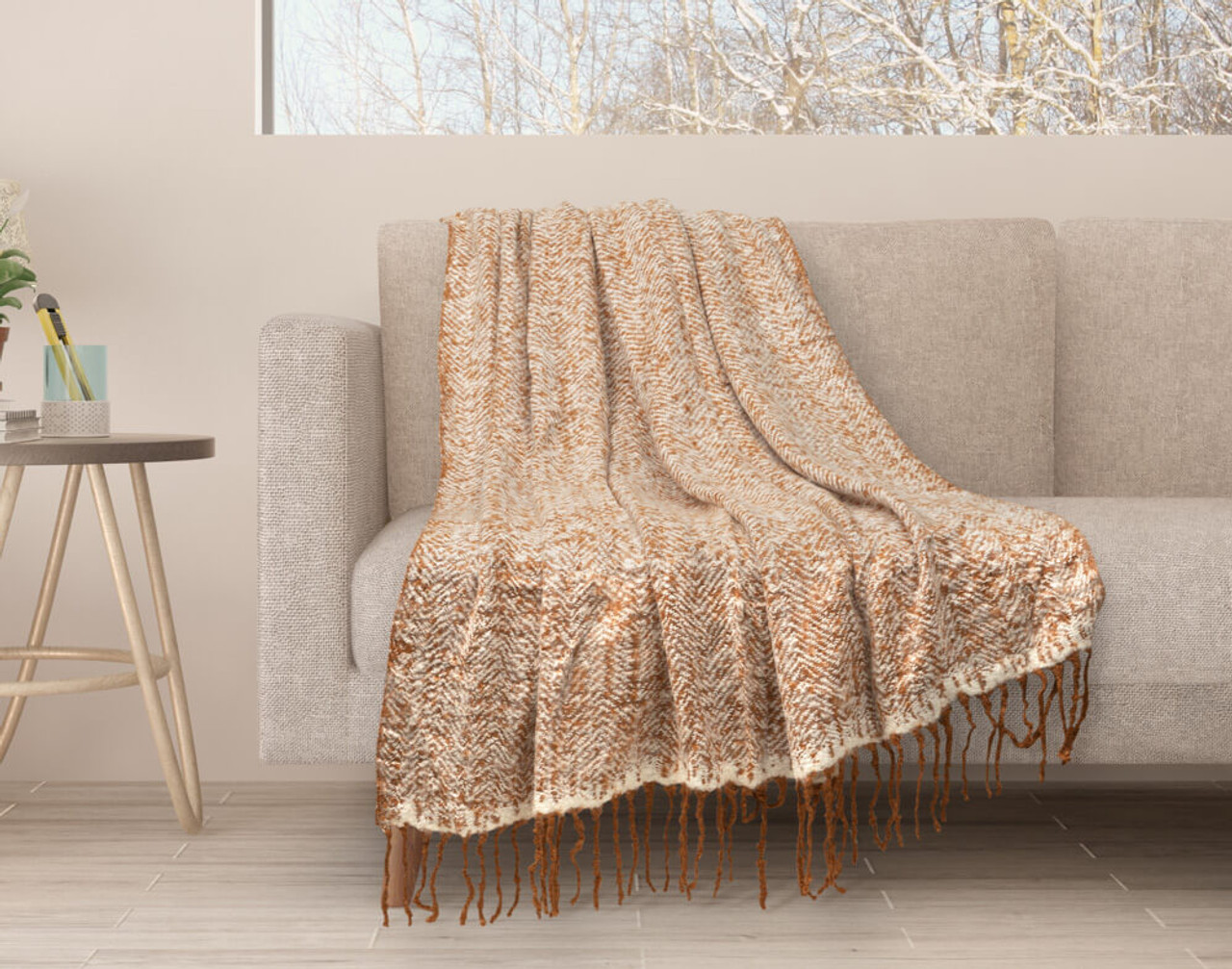 Our Copper Herringbone Knit Fringe Throw draped over a couch.