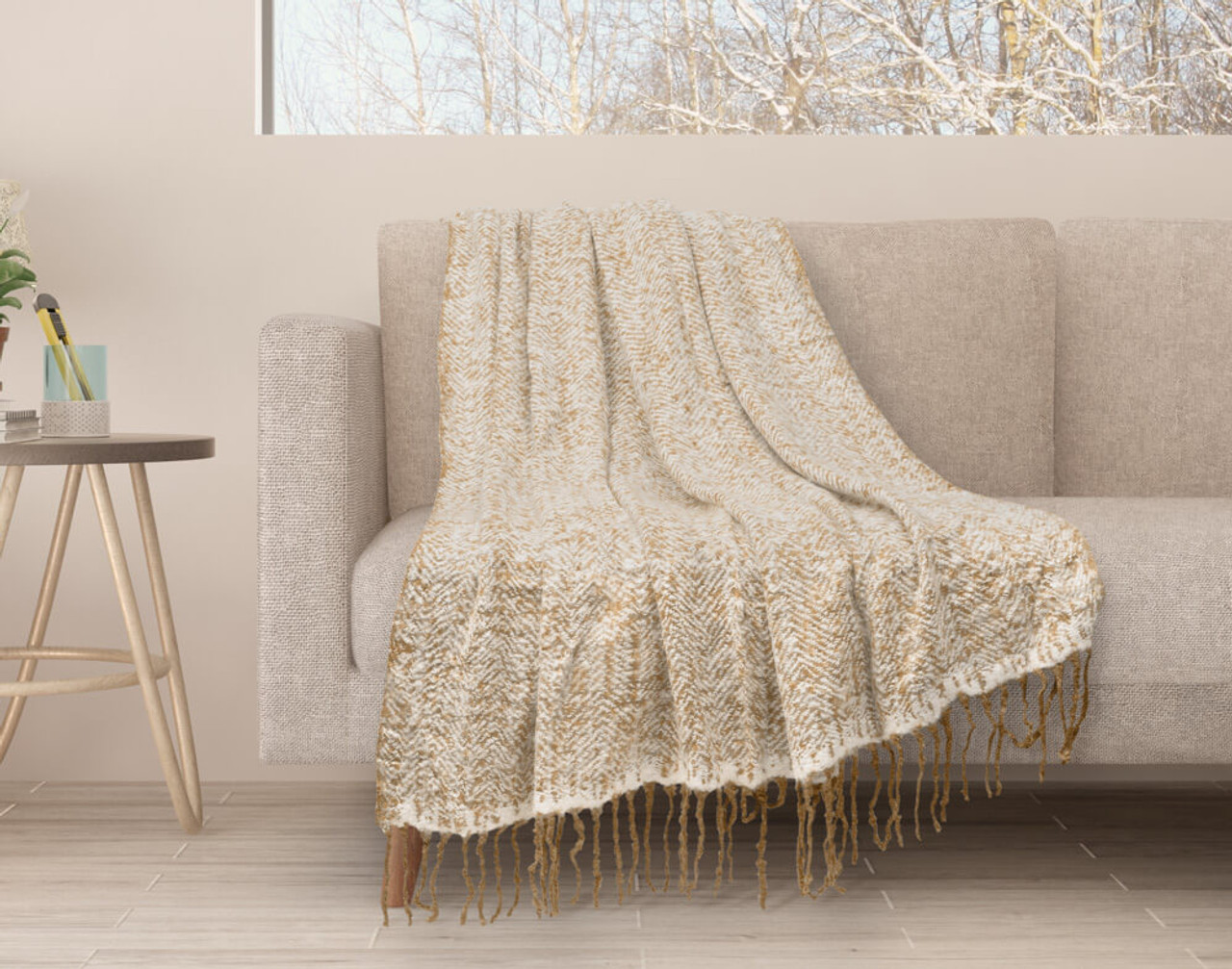 Our Oat Mix Herringbone Knit Fringe Throw draped over a couch.