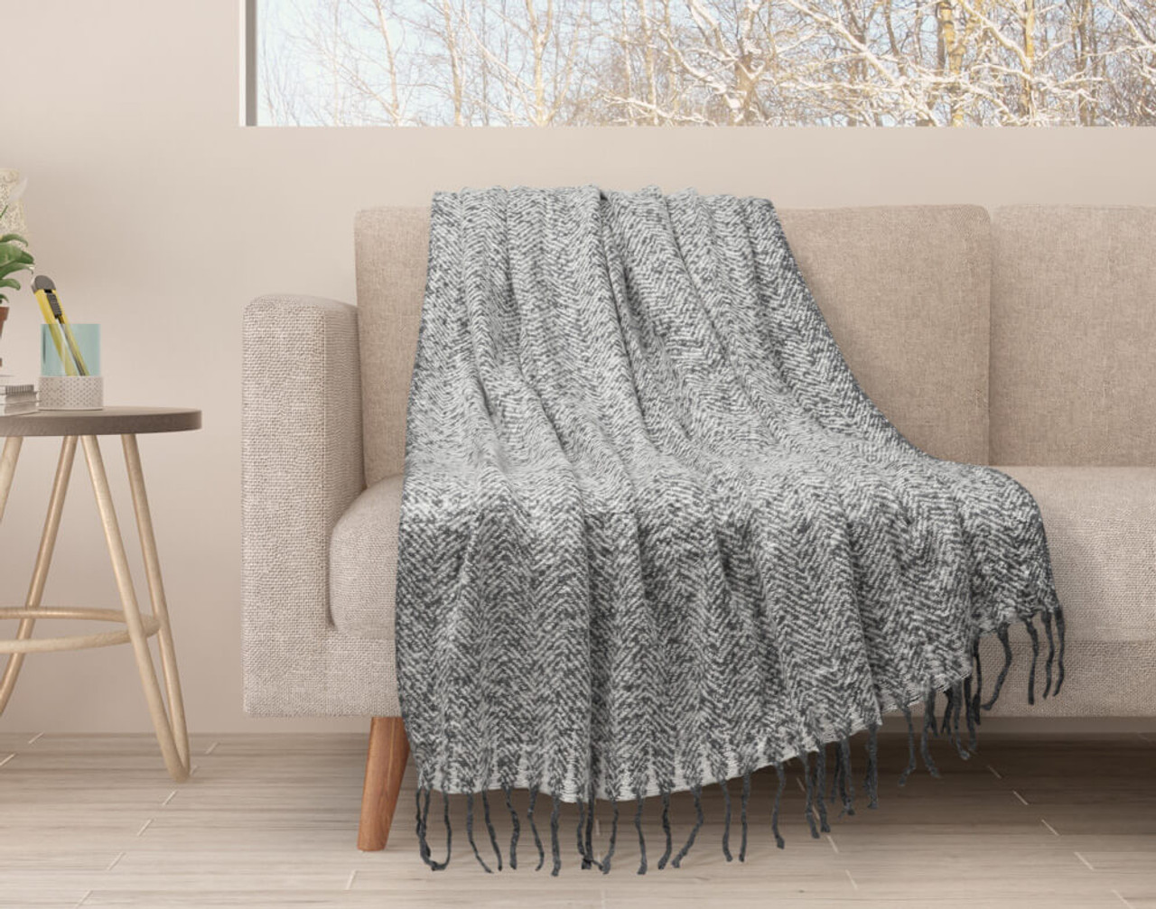 Our Grey Mix Herringbone Knit Fringe Throw draped over a couch.