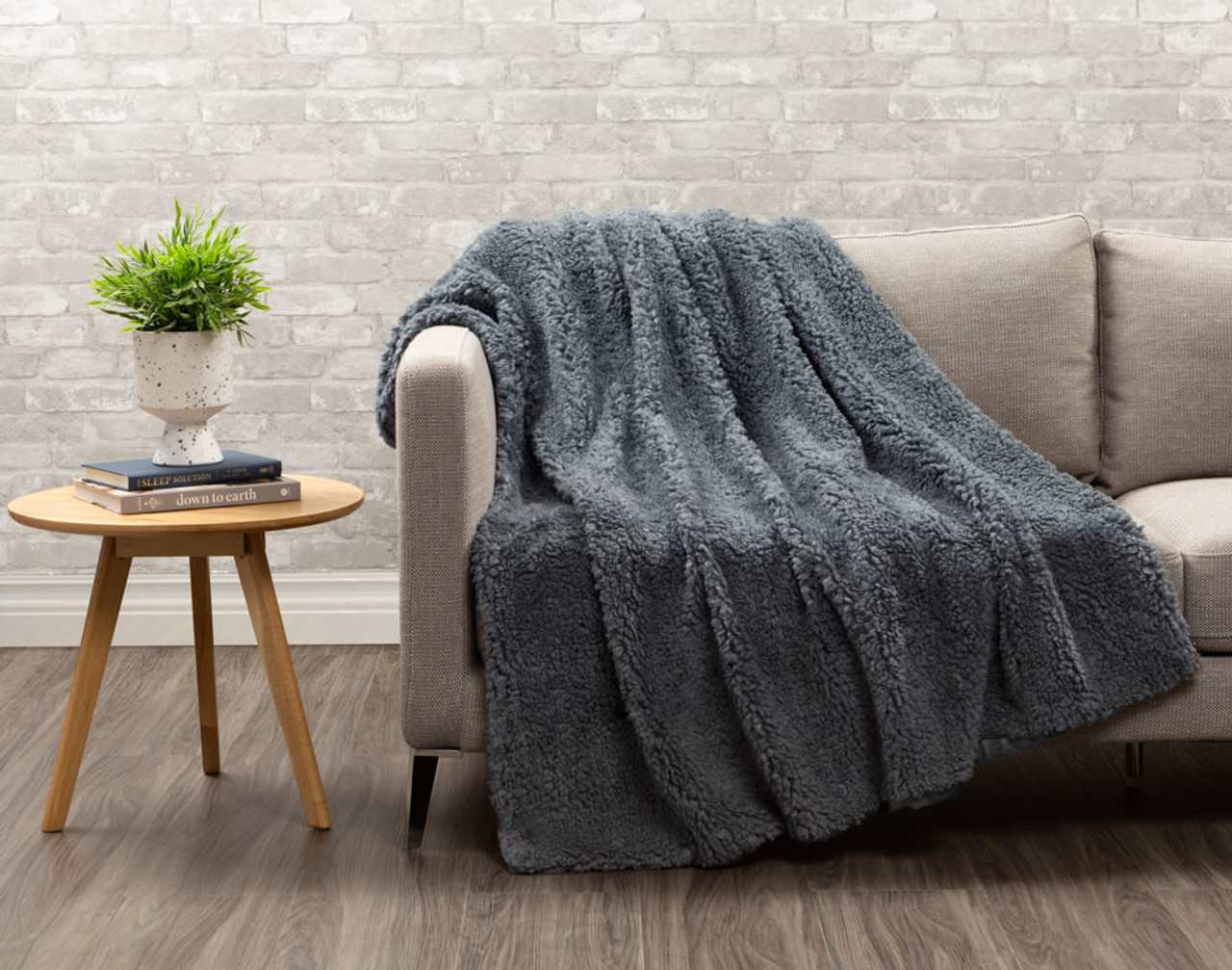 Sherpa side of Lambswool Faux Fur Throw in Thundercloud draped over a living room chair.