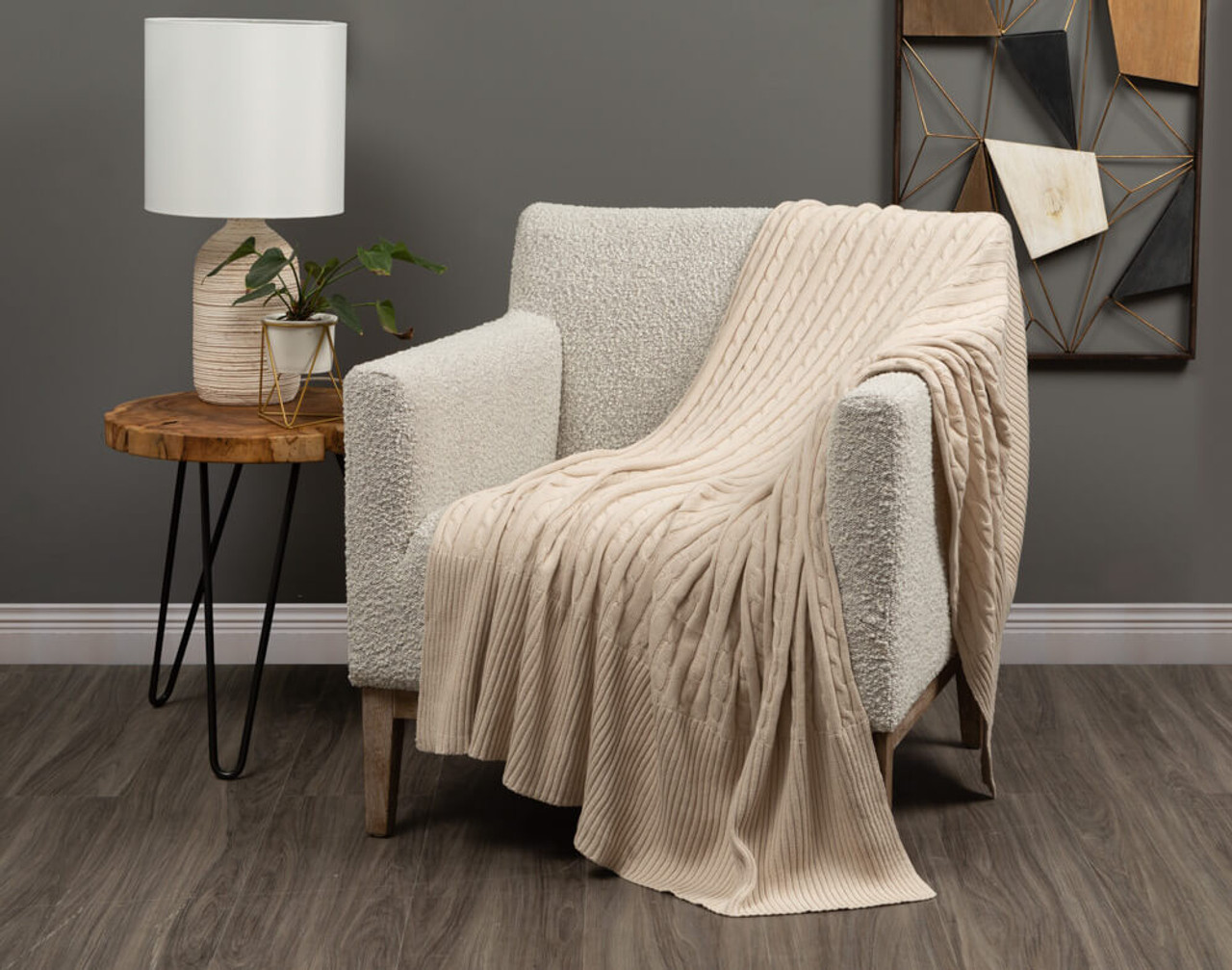 Cable Rib Knit Beige Throw in Natural draped over a living room chair.