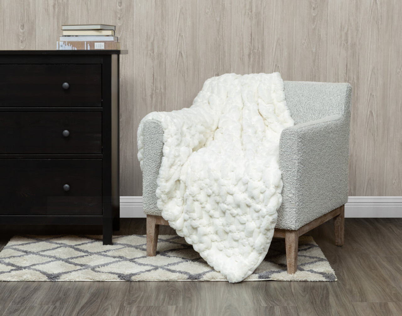 Our Carved Faux Fur Throw in Snow White, draped over a chair.