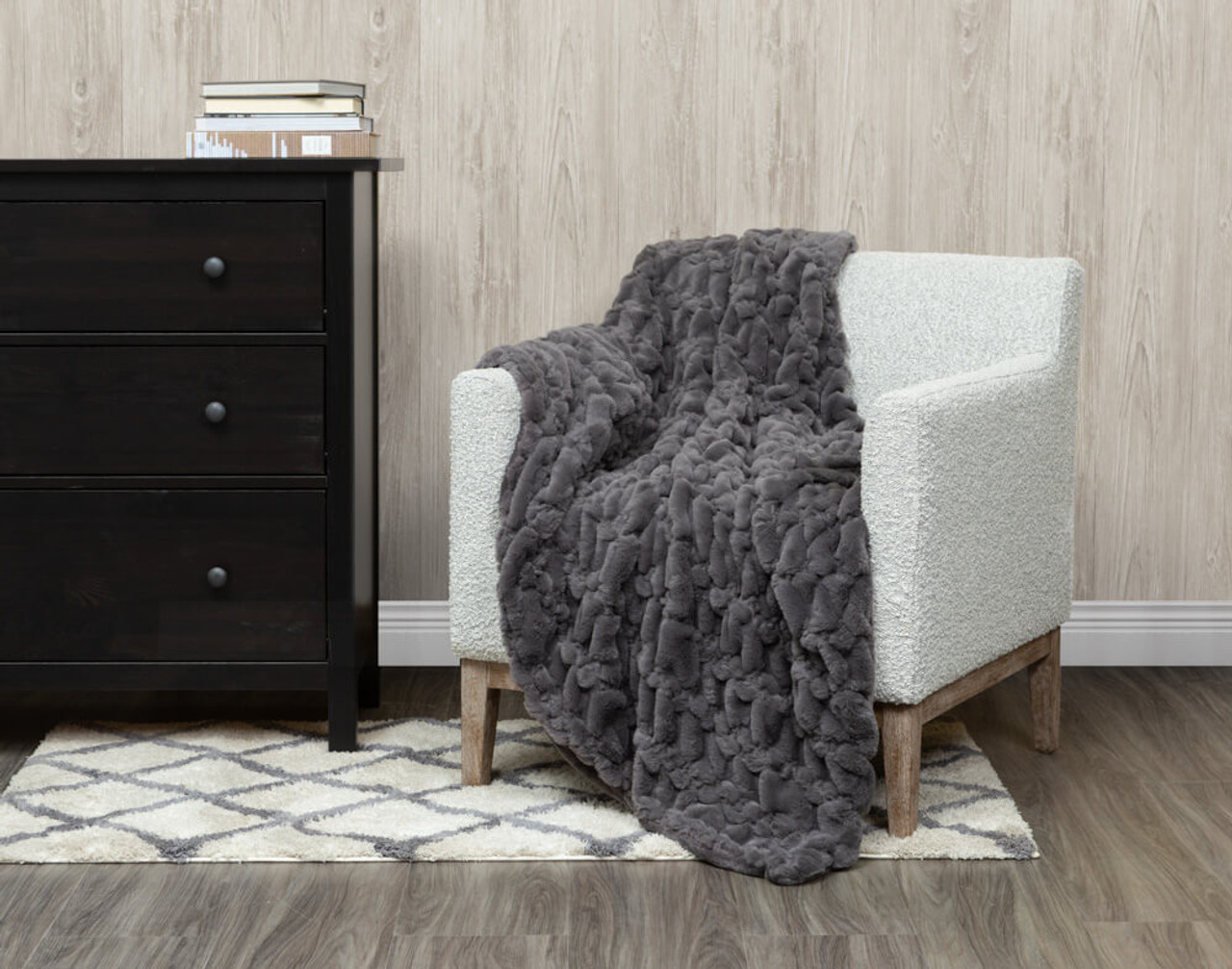 Our Carved Faux Fur Throw in Graphite Grey, draped over a chair.
