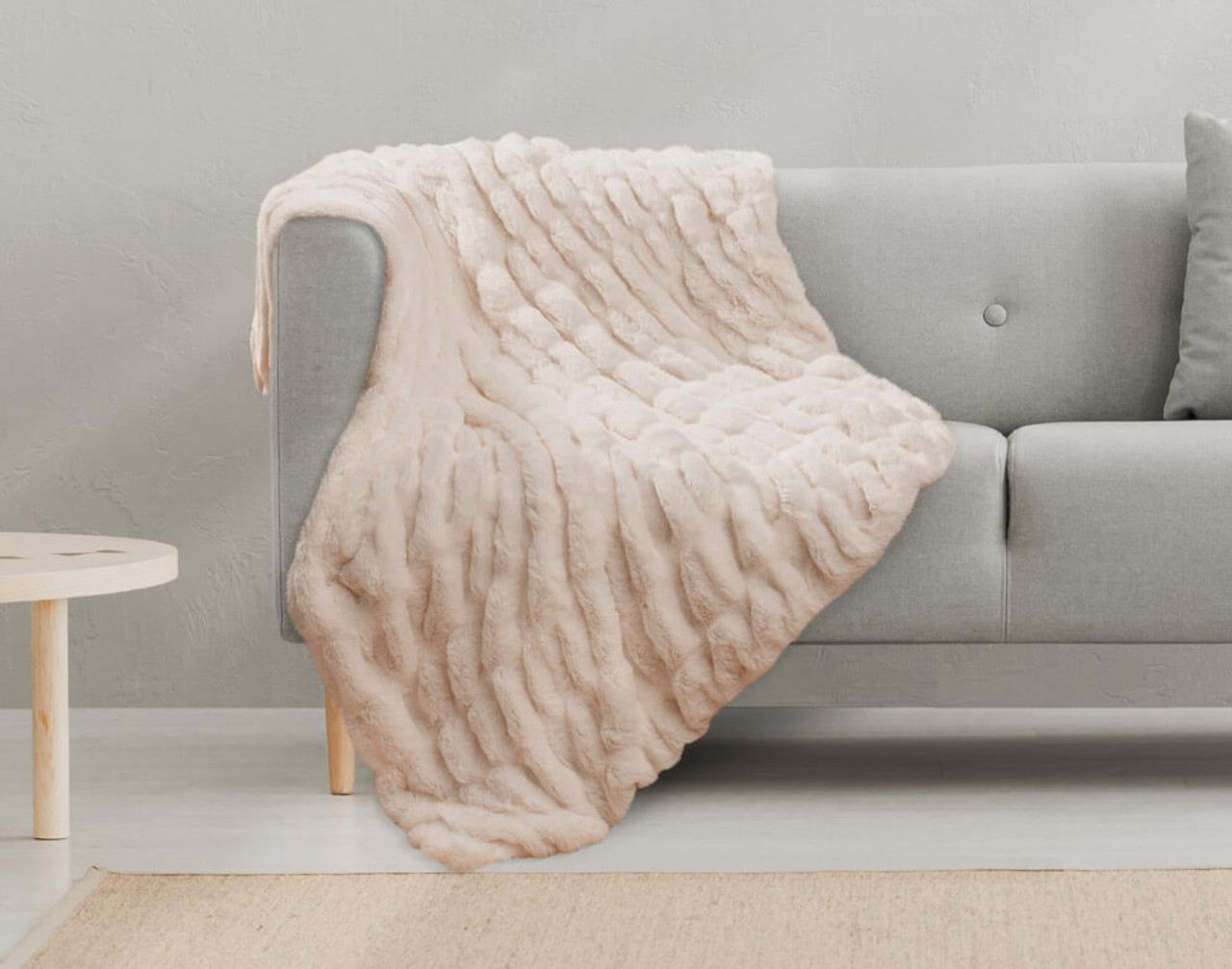 Our Rabbit Carved Faux Fur Throw in Blush Pink, draped over a couch.