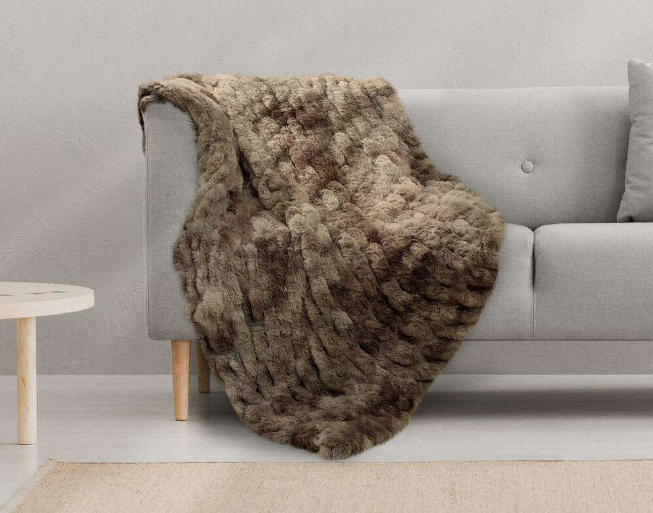 Our Rabbit Carved Faux Fur Throw in Mink, draped over a couch.