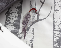 Close up of embroidered woodpecker in shades of red and grey.
