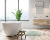 TENCEL™ Modal Bath Mat in front of a modern white bathtub.