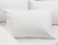 The Palma Duvet Cover Pillow Sham on bed.