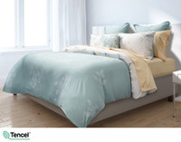 Repose Bedding Collection featuring teal and yellow leaves on a white background, seen from above.