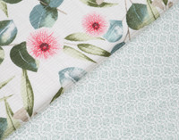 Close up of Sweeny Cotton Quilt set floral pattern in shades of green and pink on a white background that reverses to a light green geometric print