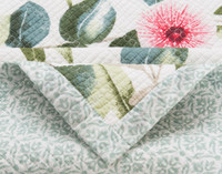 """Close up of Sweeny Cotton Quilt Set that shows both front pattern, a floral print in shades of green and pink on a white background, and reverse pattern, a light green geometric print. Front features a 1"""" trim in the same material as the reverse."""