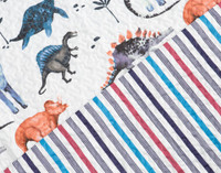 Close up of Bronto coverlet set featuring an array of dinosaurs in shades of red, grey, and blue on a white background as well as the reverse side of the coverlet which features a striped pattern in red and shades of blue.