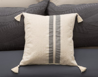 Noa Square Cushion is an off-white accent piece that features two vertical stripes in charcoal grey, slightly off center, and has tassels in each corner, pictured on a dark background.