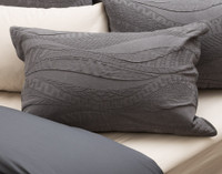 Noa Pillow Sham pictured with Bamboo Charcoal sheeting in Driftwood, a light beige.