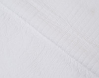 Both the front and reverse of the Dominion White Floral Cotton Quilt Set are white. The reverse features stitching that creates a striped effect.