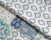 Side by side view of Bali Coverlet Set pattern, front view features a traditional patchwork quilt style in shades of green and blue, reverse features a playful teardrop pattern in blues and yellows on a white background.