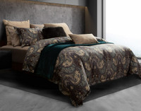 Tristan Duvet Cover features shades of brown, purple, and teal in a classic paisley print that reverses to a tan quatrefoil pattern. Shown from the side.