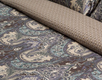 Close up of both front and reverse prints; front features a classic paisley print in brown, purple, and teal, while reverse features a tan quatrefoil design.